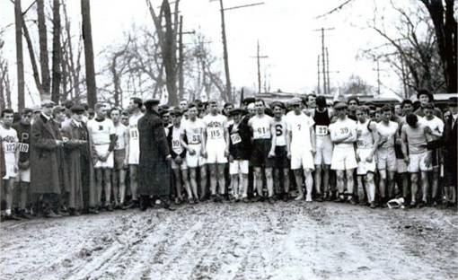 While being given instructions by race organizers, 123 men wait at the starting line of the 1912 marathon on a muddy road among bare trees. © Courtesy of the Ryan Family