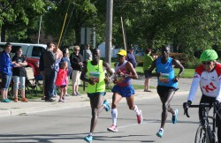 Allan Kiprono, Meb Keflezighi, and Lani Kiplagat, with KI's Dick Resch on the leading bike. © Take The Magic Step