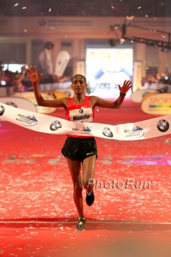 Ethiopia's Mamitu Daska raises her arms in triumph as she breaks the finish line tape. © www.photorun.net